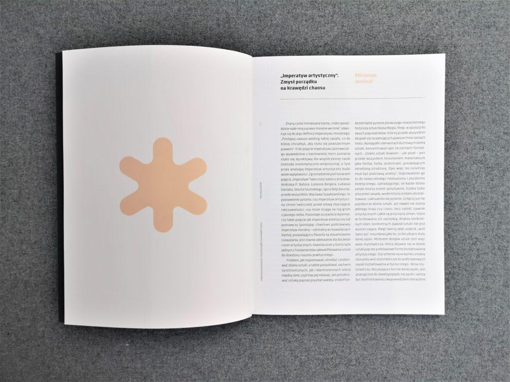 otwarty katalog leży na szarym tle, na stronie po lewej stronie kremowy znak przypominający słońce, po prawej tekst w dwóch kolumnach